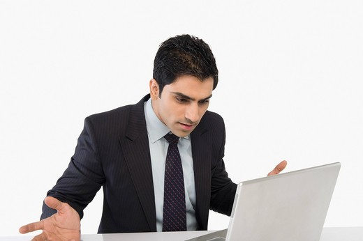 Businessman looking confused while using a laptop : Stock Photo