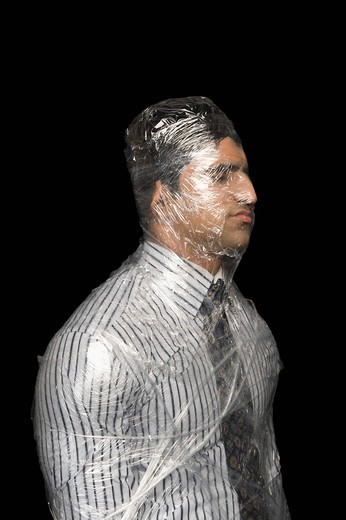 Businessman wrapped in a plastic wrap : Stock Photo