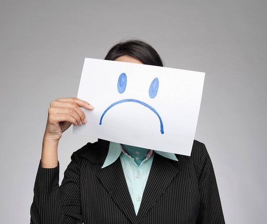 Stock Photo: 1657R-38287 Businesswoman holding a sad face in front of her face
