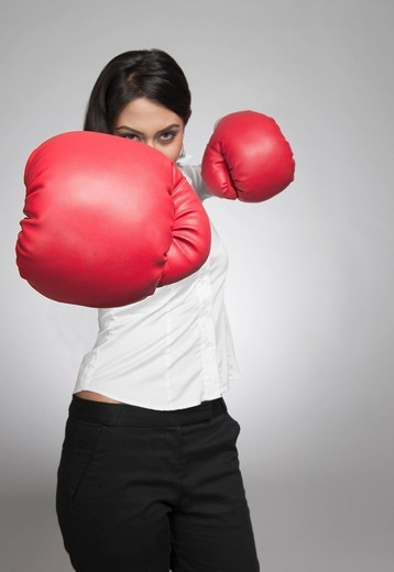 Stock Photo: 1657R-38322 Businesswoman punching with boxing gloves