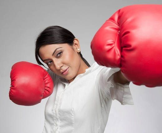 Businesswoman punching with boxing gloves : Stock Photo
