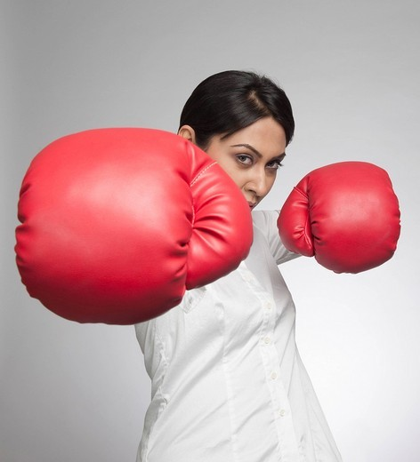 Stock Photo: 1657R-38327 Businesswoman punching with boxing gloves