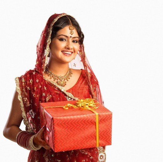 Stock Photo: 1657R-38542 Bride in traditional wedding dress and holding a gift