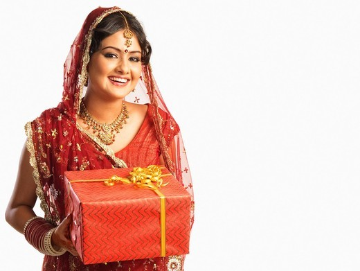 Bride in traditional wedding dress and holding a gift : Stock Photo