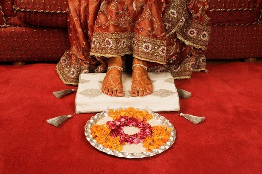 Bride´s feet with henna decoration on a cushion with pooja thali : Stock Photo