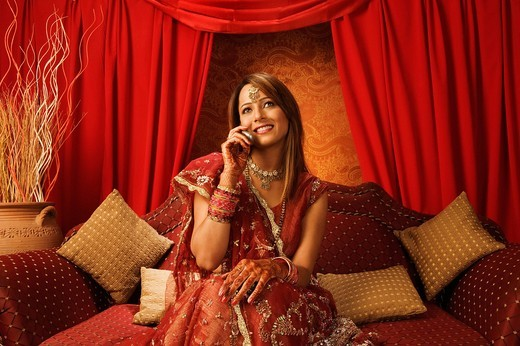 Bride in traditional wedding dress talking on a mobile phone : Stock Photo