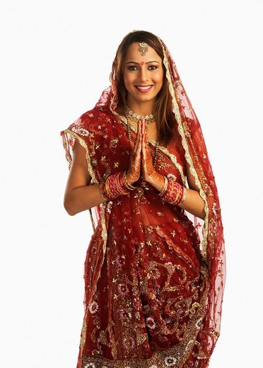 Portrait of a bride in traditional wedding dress standing in prayer position : Stock Photo