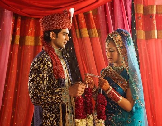 Couple performing Mala Badal ceremony in wedding mandap : Stock Photo