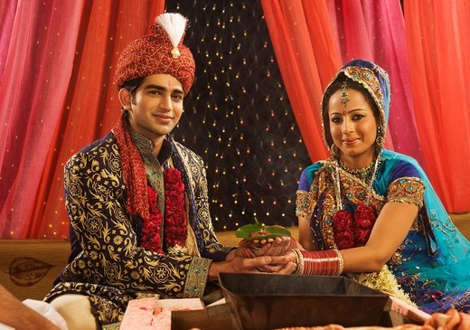 Couple performing religious ceremony in wedding mandap : Stock Photo