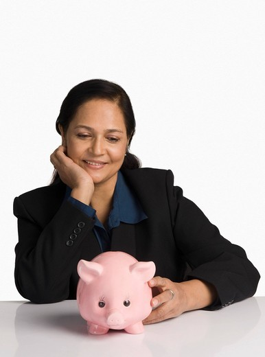 Businesswoman looking at a piggy bank and smiling : Stock Photo