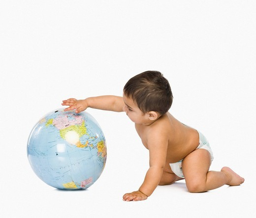 Baby boy playing with a globe : Stock Photo