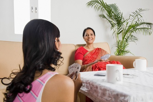 Woman playing cards with her mother : Stock Photo