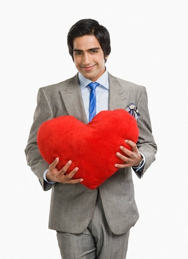 Portrait of a businessman holding a heart shaped cushion and smiling : Stock Photo