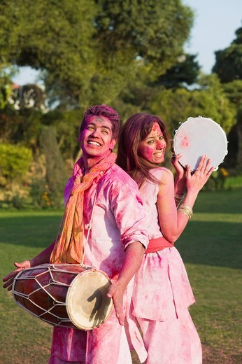 Couple celebrating Holi with musical instruments in a garden : Stock Photo