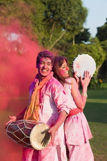 Stock Photo: 1657R-39341 Couple celebrating Holi with musical instruments in a garden