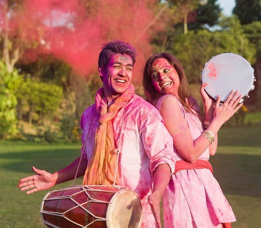 Stock Photo: 1657R-39343 Couple celebrating Holi with musical instruments in a garden