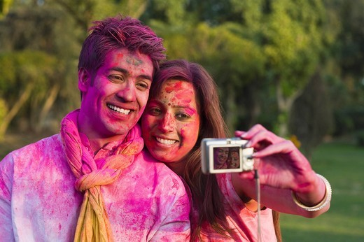 Couple taking a picture of themselves on Holi : Stock Photo