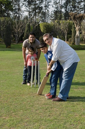 Stock Photo: 1657R-39431 Family playing cricket in lawn