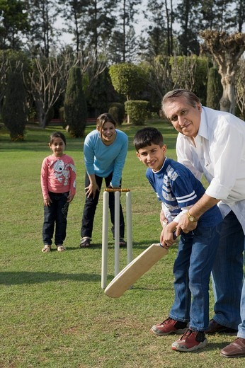 Family playing cricket in lawn : Stock Photo