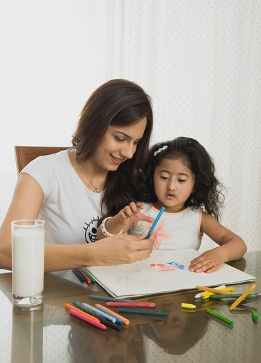 Close_up of a girl drawing with her mother at the dining table : Stock Photo