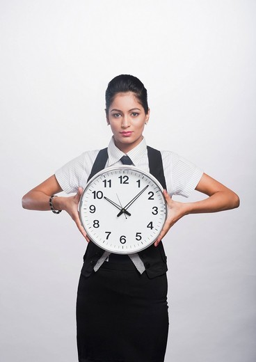 Portrait of a businesswoman holding a clock : Stock Photo