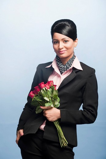 Portrait of a businesswoman holding a bouquet of flowers : Stock Photo