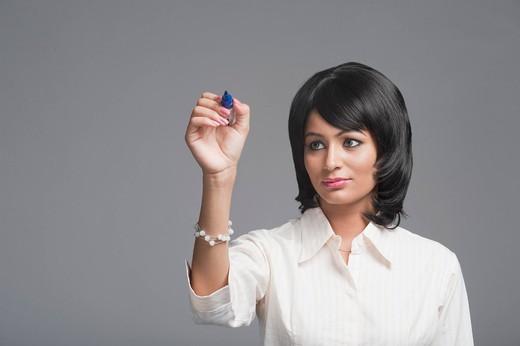 Woman holding a felt tip pen : Stock Photo