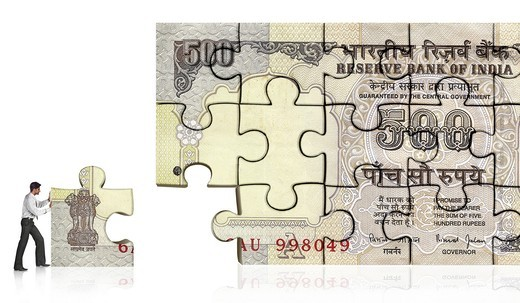 Businessman making five hundred rupee Indian banknote from jigsaw pieces : Stock Photo