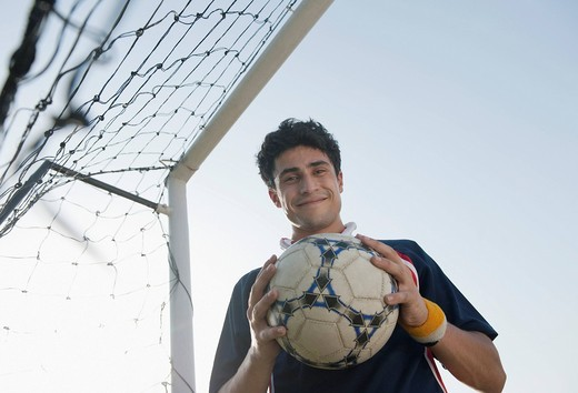 Soccer player holding a soccer ball : Stock Photo