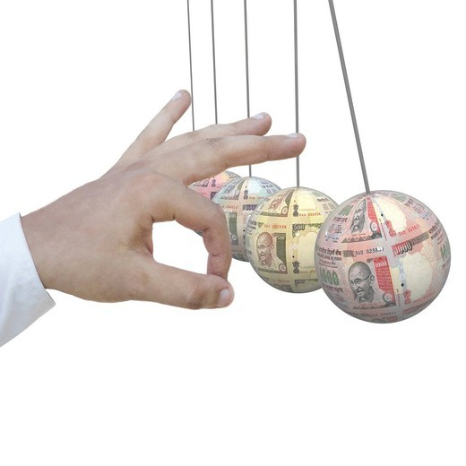 Stock Photo: 1657R-41180 Human hand striking the money pendulums in a cradle