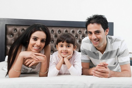 Portrait of a couple lying on the bed with their daughter : Stock Photo