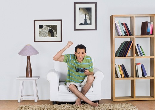 Stock Photo: 1657R-42245 Portrait of a man cheering while playing a video game