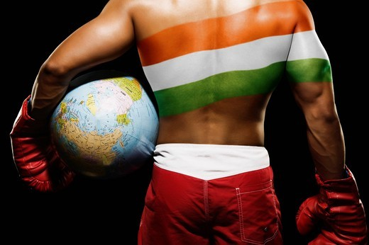 Rear view of a male boxer holding globe with Indian flag painted on his back : Stock Photo