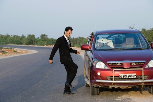 Stock Photo: 1657R-42709 Businessman kicking a broken down car at the roadside