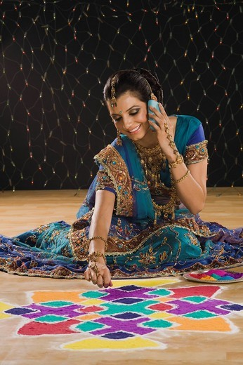Woman talking on a mobile phone and making rangoli : Stock Photo