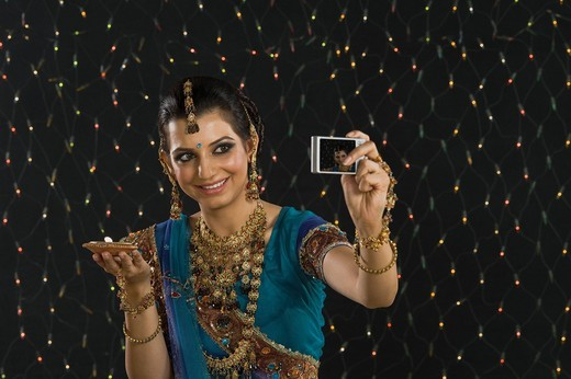 Woman holding an oil lamp and taking a picture of herself with a digital camera : Stock Photo