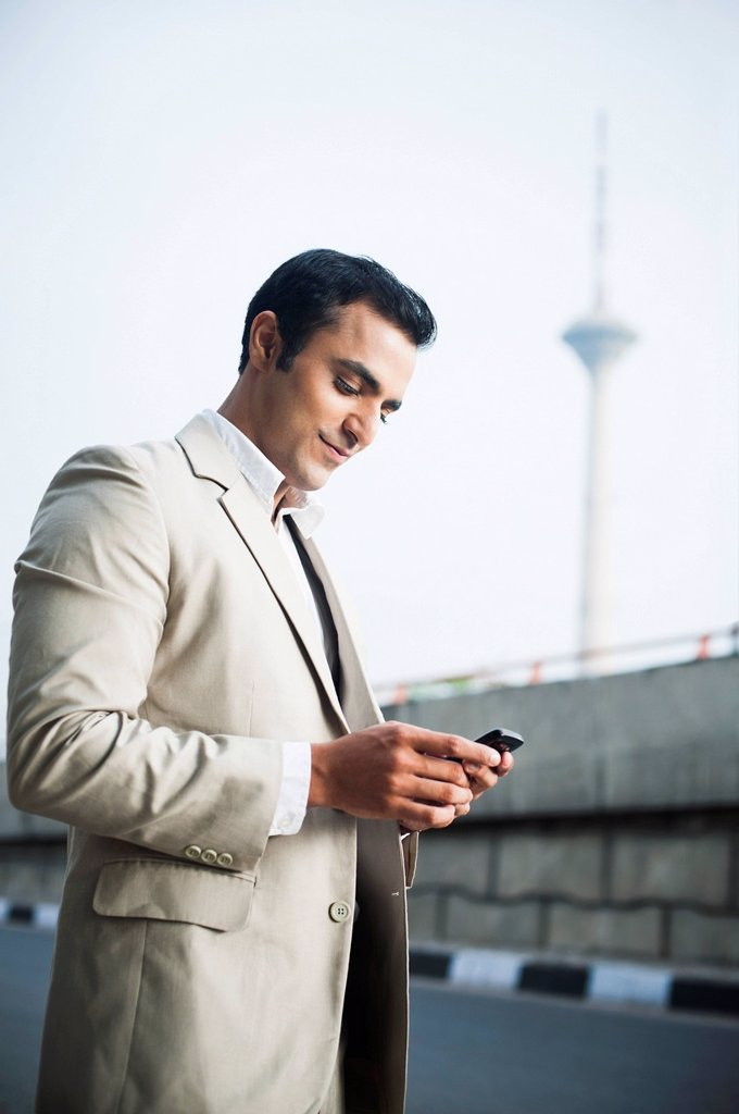 Stock Photo: 1657R-44998 Businessman text messaging on a mobile phone at roadside