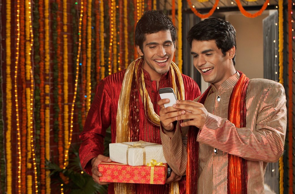Male friends text messaging on a mobile phone on Diwali : Stock Photo