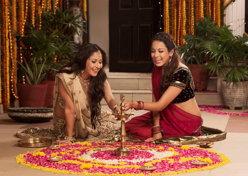 Female friends lighting oil lamps on Diwali : Stock Photo