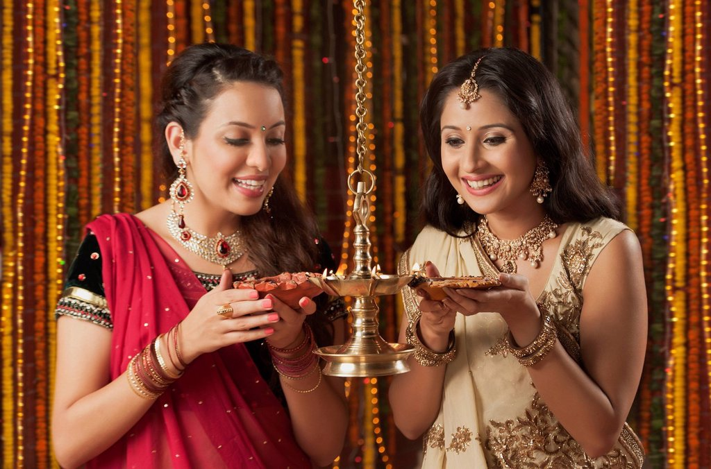 Female friends burning oil lamps on Diwali : Stock Photo