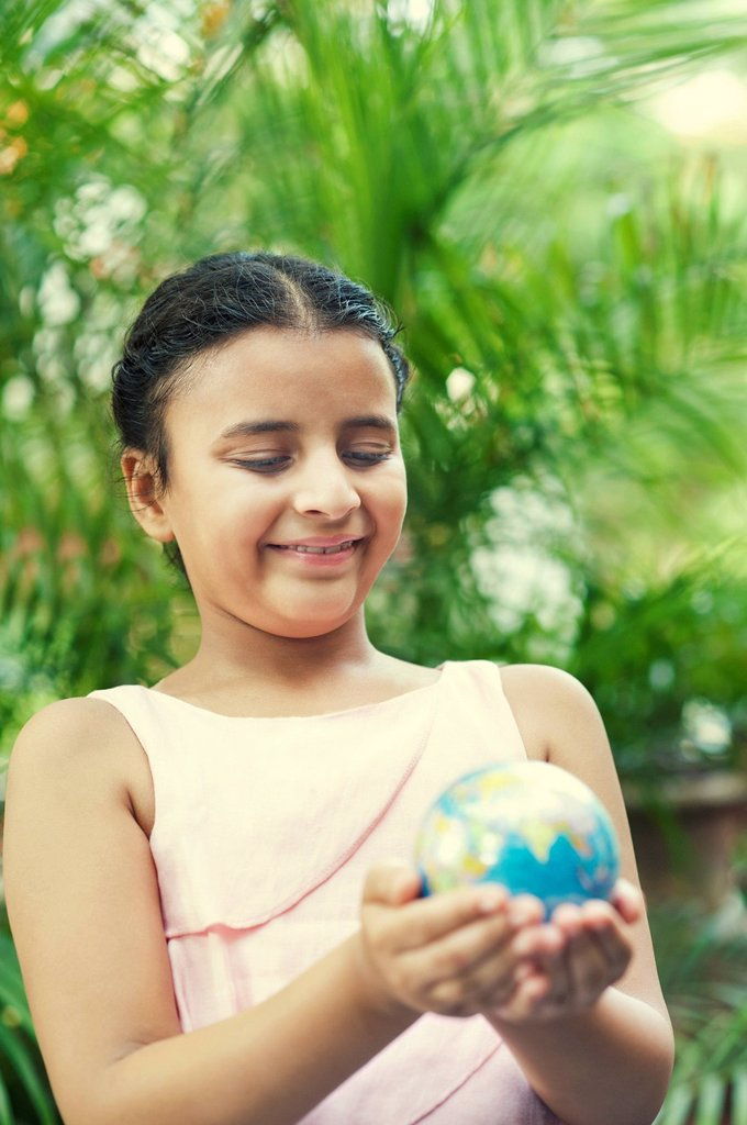 Stock Photo: 1657R-47492 Close-up of a smiling girl holding a globe