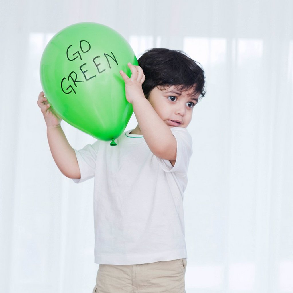Stock Photo: 1657R-47933 Baby boy playing with a green balloon