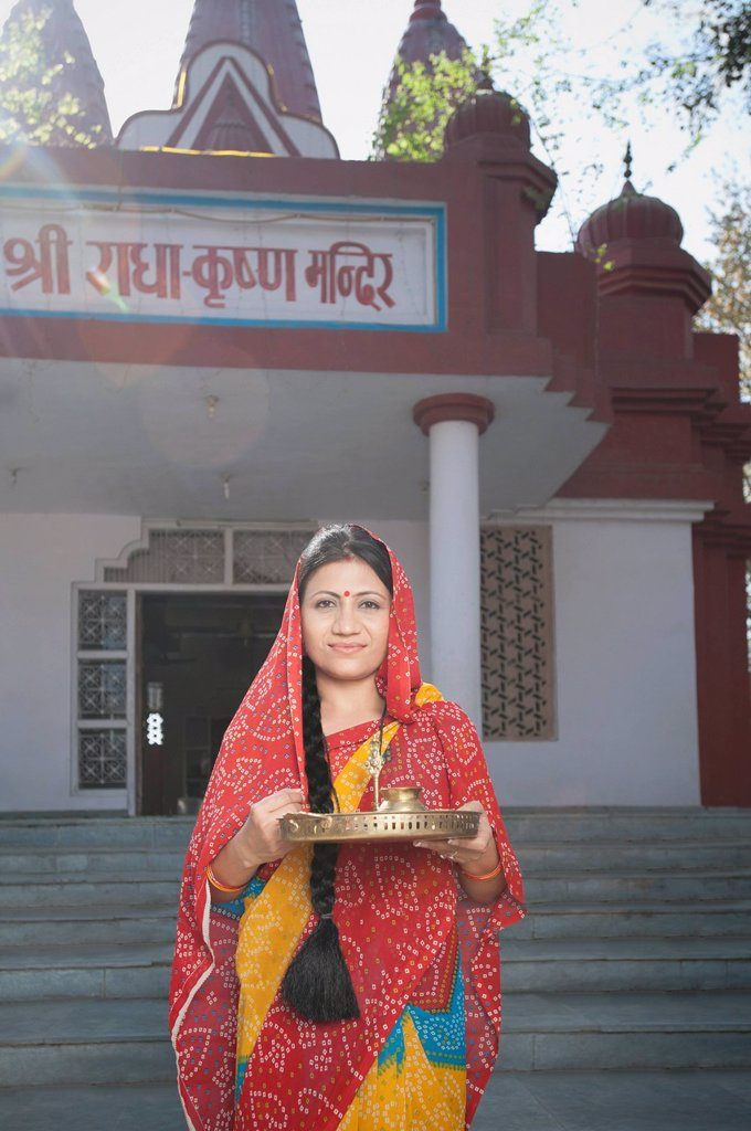 Stock Photo: 1657R-51853 Woman standing in front of a temple, Sohna, Haryana, India