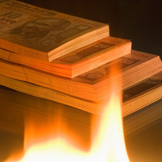 High angle view of a stack of Indian banknotes of different denominations near a flame : Stock Photo