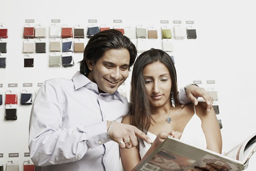 Close-up of a young couple choosing fabric swatches from a magazine : Stock Photo