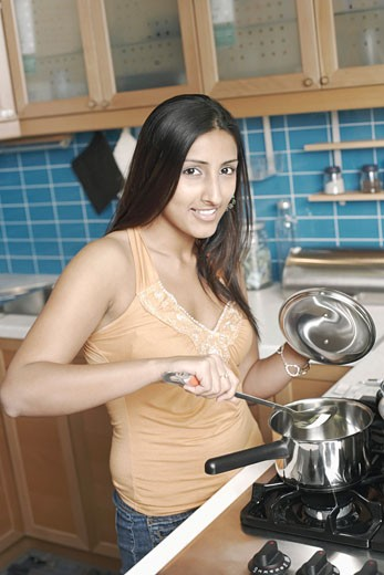 Portrait of a young woman cooking in the kitchen : Stock Photo