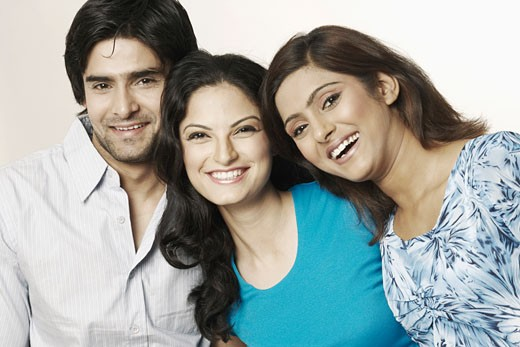 Portrait of two young women and a young man smiling : Stock Photo