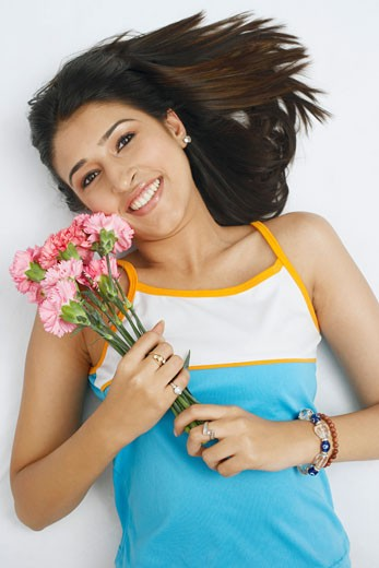 Portrait of a young woman lying on her back and holding a bunch of flowers : Stock Photo