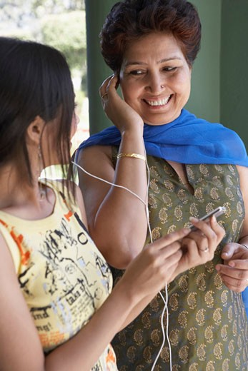Stock Photo: 1657R-7805 Close-up of a mature woman and her daughter listening to an MP3 player