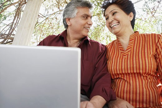 Low angle view of a mature couple sitting in front of a laptop : Stock Photo